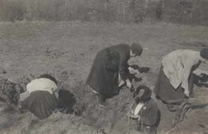 Women searching a bomb crater for souvenirs in France