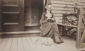 Betsy Wilder seated on piazza, with dog at her feet