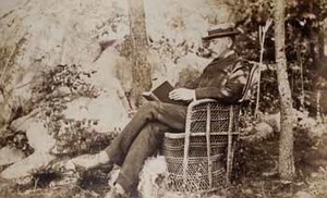 James Lowndes at Beverly Farms, seated outdoors in wicker chair, reading book, with dog at feet