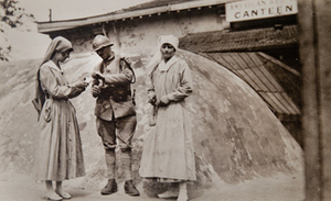 Two Red Cross workers offering cigarettes to a soldier outside a canteen