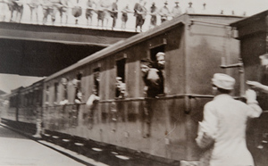 Soldiers leaning out of windows of a train in a station with a bridge overhead