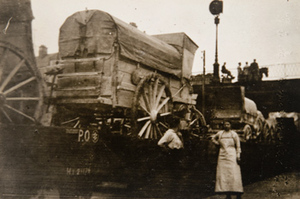 Two civilians standing in front of covered wagons being transported on railroad flat cars