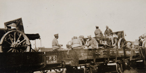 Artillery and soldiers on a railroad flat car