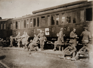 Soldiers gathered alongside a stationary train [marked with a Red Cross?]