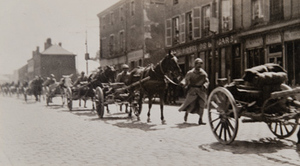 Street-level view of soldiers and horse-drawn artillery marching through a town