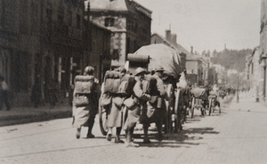 Street-level view of soldiers in full kit and horse-drawn artillery marching through a town