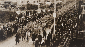 View from above of a military procession and civilians crowded along the street
