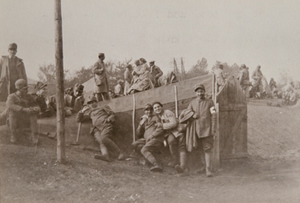 View of soldiers sitting in front of a dugout shelter