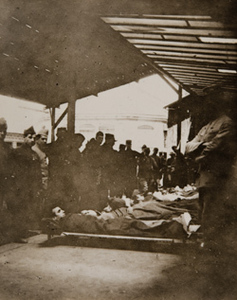 Group of soldiers-some on stretchers-on a train platform