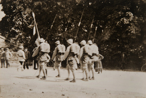 View of soldiers with bayonets marching along a tree-lined street as civilians look on