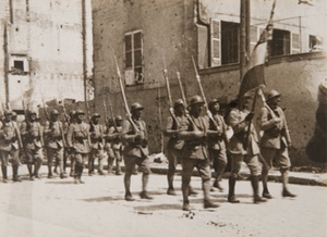 View of soldiers with bayonets marching along a town street