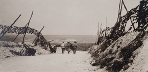 Three soldiers walking down a road flanked by camouflaged embankments