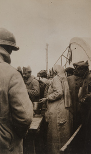 Red Cross worker serving food to a crowd of soldiers