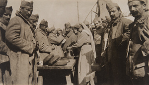Red Cross worker serving bread and coffee to a crowd of soldiers