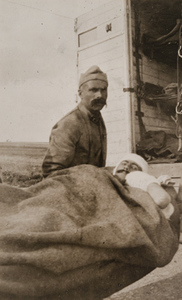 Wounded man on a stretcher in front of an ambulance