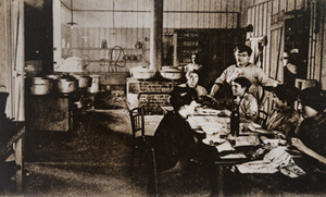 Group of women sitting around a table in a canteen kitchen