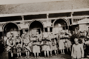 Group of soldiers in full kit standing in front of a canteen