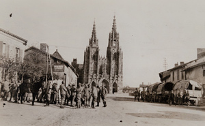 Group of soldiers and covered wagons on a town street in front of a cathedral, L'Épine, October 1918