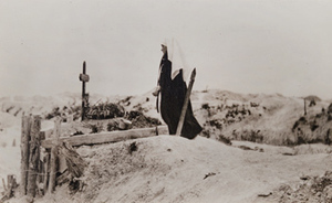 Red Cross worker next to a grave marked with a cross and a wreath, Fort de la Pompelle