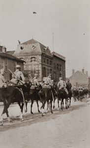 Street-level view of mounted soldiers riding through a town street