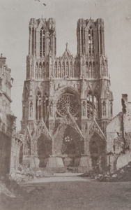 Exterior view of the front of a cathedral showing damage, Reims