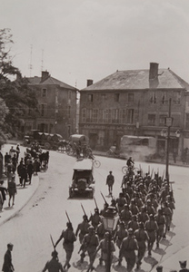 Soldiers carrying bayonets march through a town street