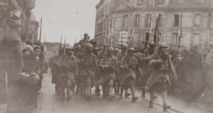 Soldiers of the 106th Regiment with bayonets march through a street lined with civilians, Châlons