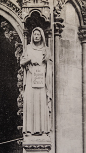 "Close-up view of a church exterior, showing a stone statue of a robed figure holding a tablet reading ""sic transit gloria mundi"", Metz"
