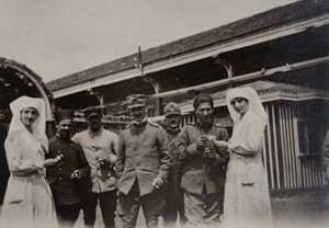 Two Red Cross workers offering cigarettes to five soldiers in front of a canteen