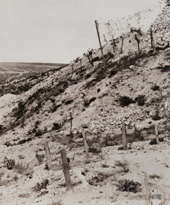 View of wooden crosses marking graves alongside a bunker and barbed wire