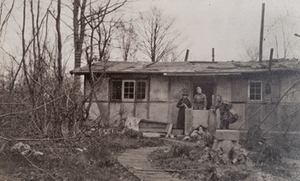 Two soldiers and one Red Cross worker in front of an abandoned bungalow