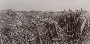 Ground-level view of a trench with barbed wire and a small cross visible on the horizon, Fort Douaumont
