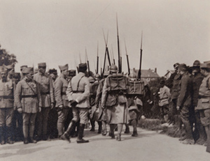 Street-level view of soldiers in full kit marching away from the camera between crowds of soldiers on either side