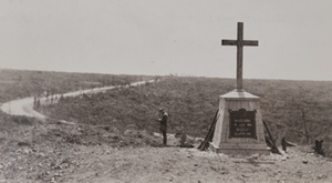 Rifles leaning against a large monument of a cross guarded by soldier, with fields and road in the background, Bayonet Trench, Verdun