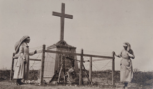 Two Red Cross workers standing next to a large monument of a cross, surrounded by barbed wire, Bayonet Trench, Verdun