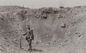 Soldier standing in large shell hole