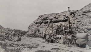 Soldiers sitting outside a large bunker with makeshift kitchen, entrance to Fort Douaumont