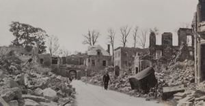 Civilian walking along a town street lined with damaged stone buildings