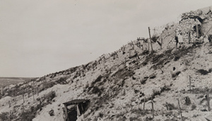 Red Cross worker walking along a war-torn hillside above barbed wire and a dugout entrance