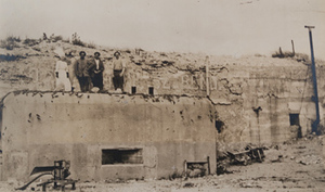 One Red Cross worker and three men standing on top of a concrete machine-gun bunker at La Laufée