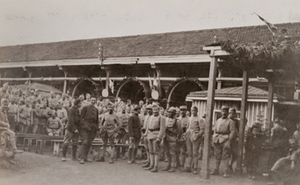 Large group of soldiers posing for a photo in front of a canteen