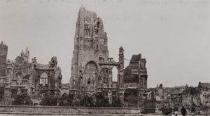 Civilians walking past the remains of a destroyed stone church with damaged buildings in the background