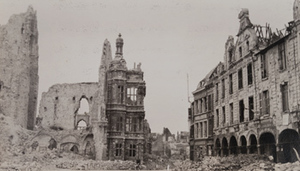 Cyclist pedaling through a street with a destroyed church on one side and badly damaged buildings on the other, Arras