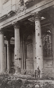 Two soldiers standing in front of a damaged building with columns pockmarked from artillery fire , Arras
