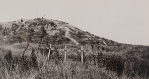 Three wooden crosses in a grassy field and more crosses on the top of a small hill in the background, Butte de Warlencourt