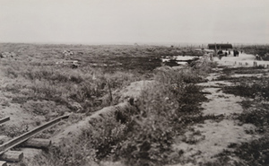 Damaged tanks visible lying in a field along a roadside and a narrow gauge railway, Menin Road, between Ypres and Menen