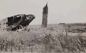 Overturned tank lying in a field next to a destroyed tree stump and a plank road, Menin Road, between Ypres and Menen