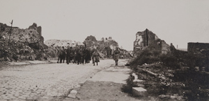 Soldiers walking along a cobblestone steet surrounded by destroyed stone buildings on both sides
