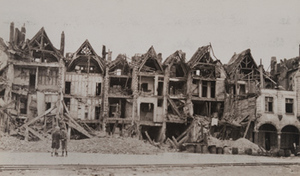 View of two children on a street in front of a row of completely destroyed houses and a narrow gauge railway in the foreground, Armentières