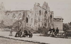 View of boys sitting on the sidewalk in front of an empty monument pedestal and a destroyed stone church in the background
